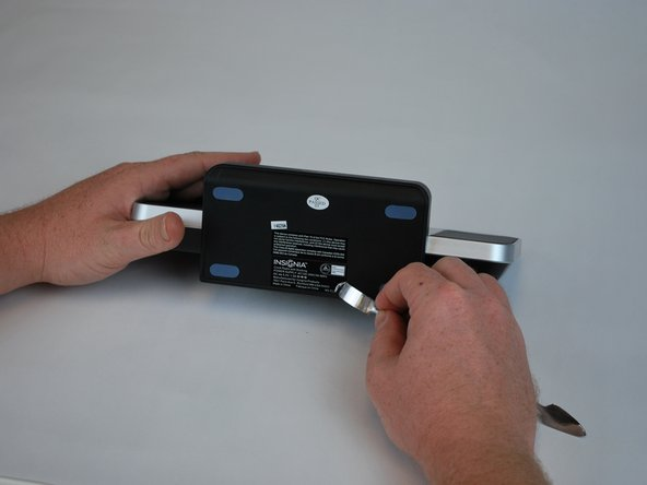 Begin by using a metal spudger to peel back the adhesive sticker and locate the screw beneath the sticker.