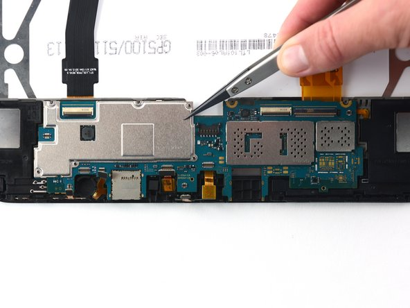 Use nylon-tipped tweezers to remove the motherboard.
