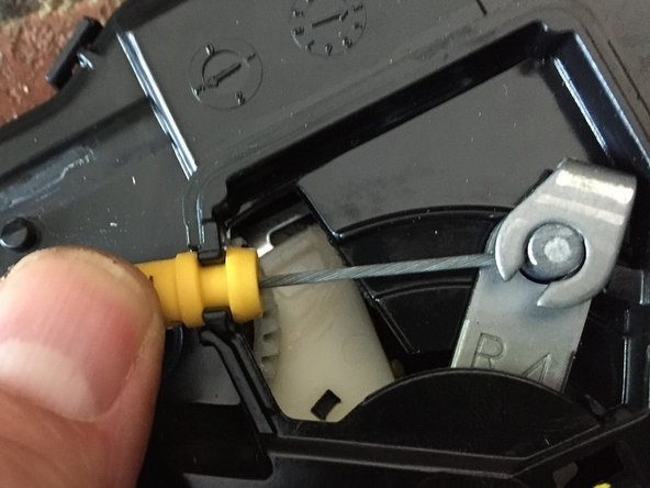 Lift the yellow cable barrel upward from the plastic holder where it enters the cavity that was protected by the removed flat plastic cover.
