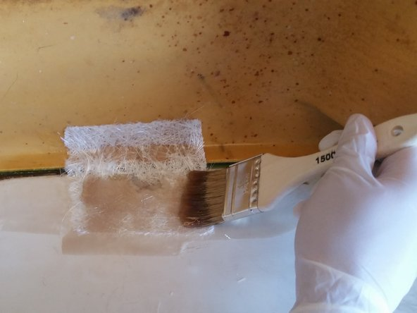 Image 3/3: Continuing with the brush, apply more resin onto the fiberglass until it is entirely soaked.