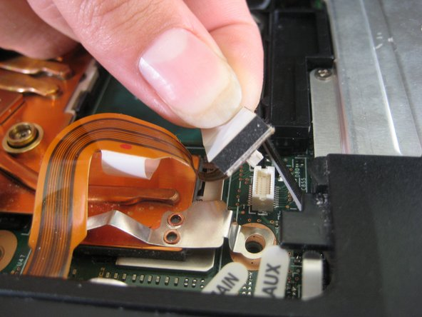 Débranchez le câble ruban du trackpad en tirant sur l'extrémité en plastique blanc.