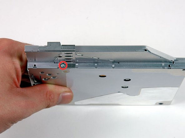 Image 1/1: Rotate the drive and remove the single Phillips screw securing the mounting bracket to the right side of the optical drive.