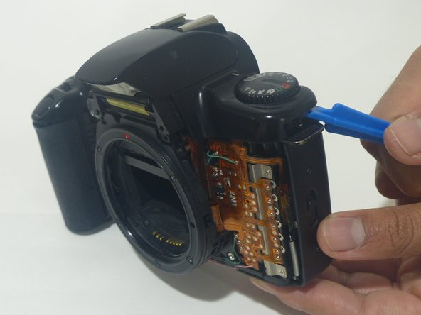 Using an opening tool (you can also use your nails, but try not to use something potentially damaging to the camera such as metal), separate the top cover from the rest of the camera!