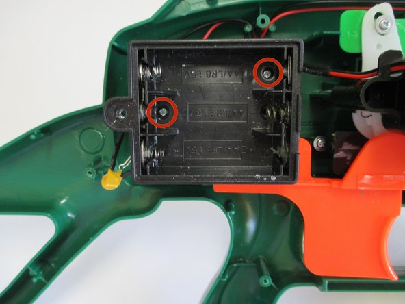 Remove the two 1/16 in. screws attaching the battery box to the frame of the gun using a Phillips #00 Screwdriver.