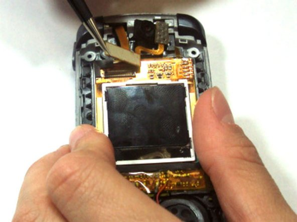 Grasp the phone with one hand, and use the tweezers with the other hand to pull up on the flex cable disconnecting it from the screen.