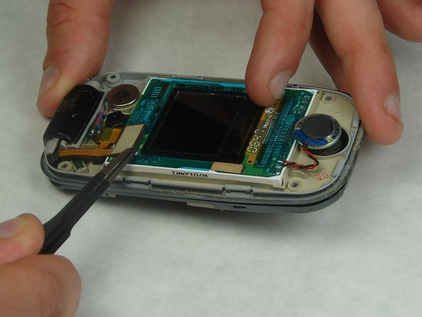 Using tweezers, carefully disconnect the display ribbon cable from the screen assembly and phone by lifting up on both connections.