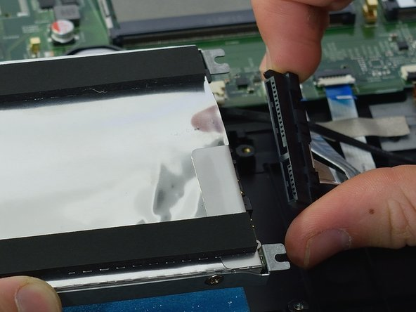 Lift the HDD case up, and gently pull at the sides of the connector to disconnect it.
