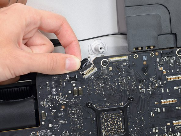 This is a delicate connection that can easily be broken. Be sure to pull the camera cable connector straight out of its socket, toward the top of the iMac.
