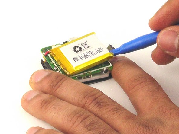 Using the plastic opening tool, gently pry the edges of the battery away from from the circuit board.