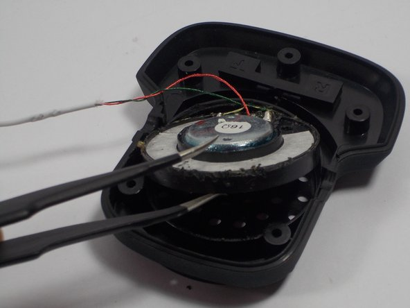 Remove the speaker from its circular shaped slot.