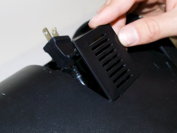 Remove grate that holds the power cord as pictured.