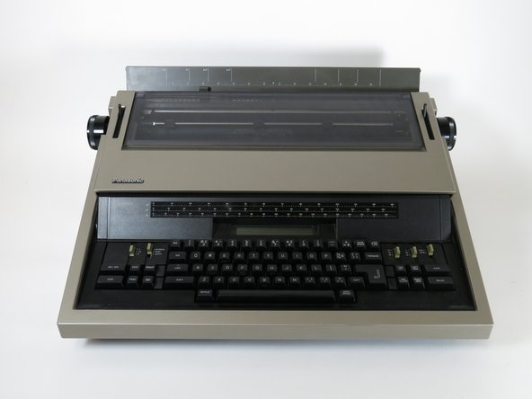 Flip the typewriter to expose the bottom body panel.