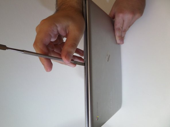 Starting at the center front of the laptop, insert the metal spudger between the keyboard panel and the bottom panel, separating the bottom panel from the laptop.