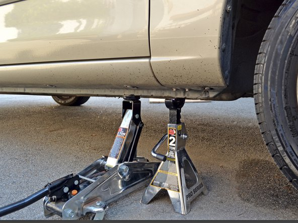 Image 1/3: Place the jack back under the car's subframe and raise the car until the jack stand is no longer supporting it.