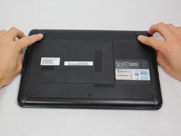 Lay the laptop  on a flat surface, bottom side up and slide the two battery release latches toward the outside of the case.
