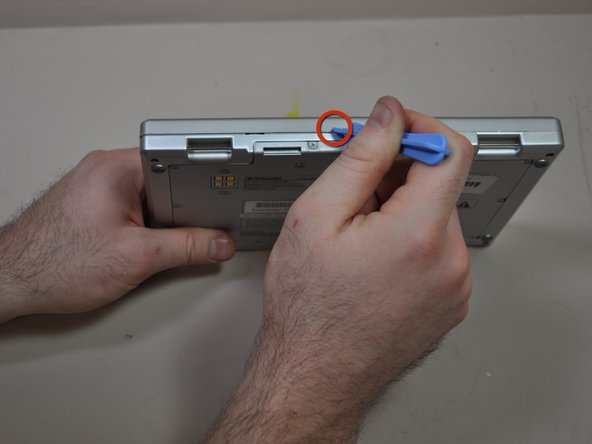 Image 1/2: In this position you will see a crease line between the device and the top cover. Gently Insert your blue plastic opening tool into the crack of the crease line, between the front and back cover to separate them.