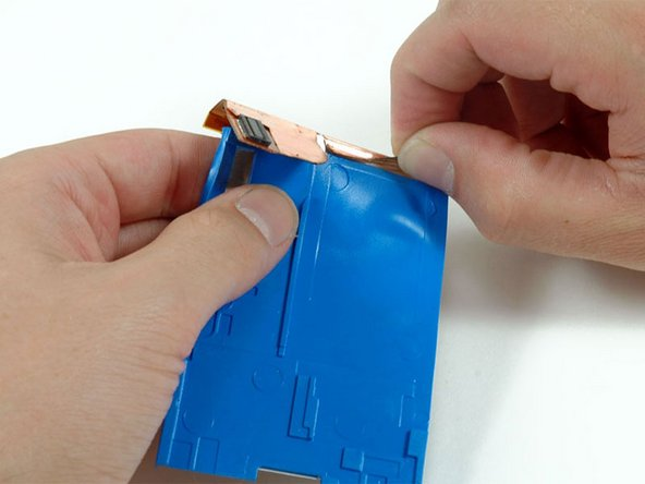 Peel up the metallic tape holding the hard drive ribbon to the blue mounting bracket.
