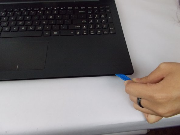 Using a small prying or opening tool, stick the prying tool under the edge of the laptop.