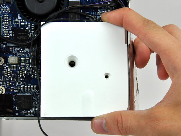 Lift the right speaker out of the rear case and move it out of the way.