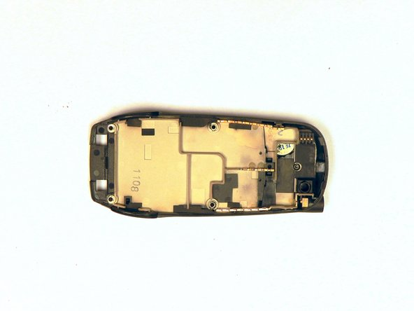 Image 2/3: Remove the 2 mm screw from the top of the inner back casing of the phone.