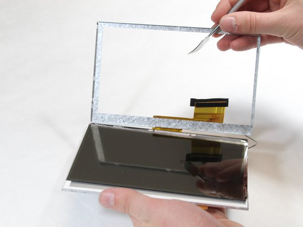 Separate the LCD screen from the metal protecting case with the metal spudger.