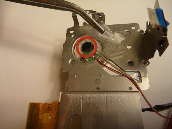Image 1/3: Remove the tape holding the speaker down by lifing with tweesers.