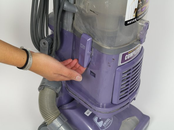 Lift the latches on both sides of the vacuum to release the dust canister.