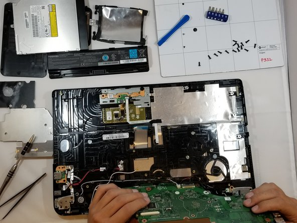 Flip motherboard over, and using the precision tweezers, disconnect the two ribbon cables.