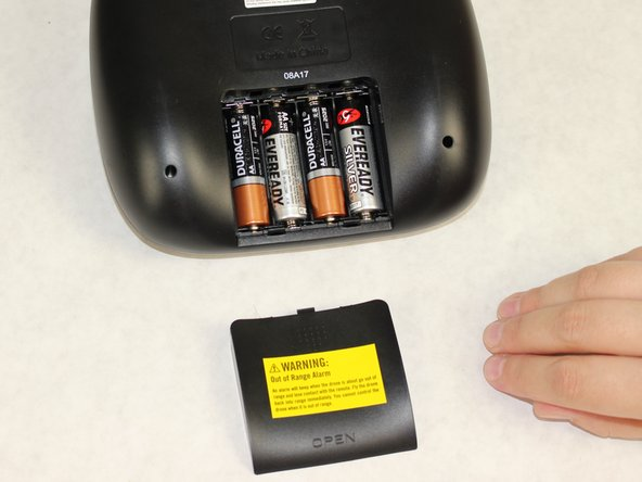 Slide the remote battery cover down to reveal the AA batteries.