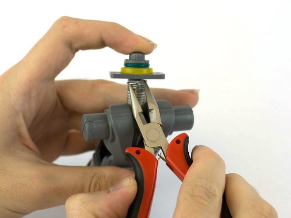 Use needle nose pliers to compress metal clamp .