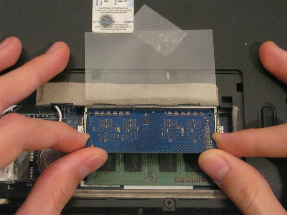 Hold on to opposite edges of the RAM chip and gently pull it diagonally upwards to remove it from the computer.