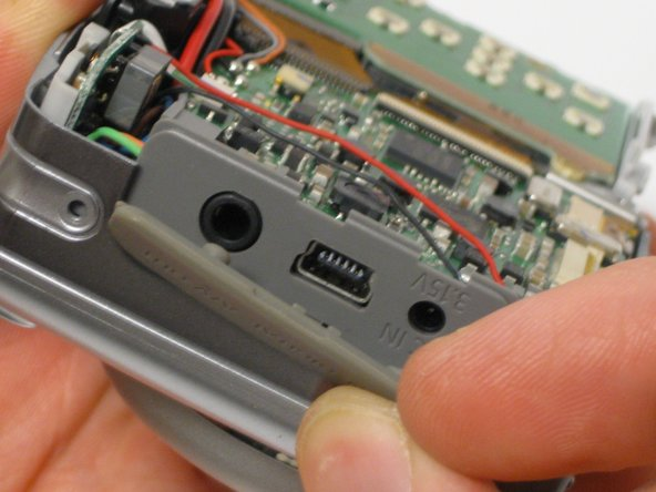 Image 1/3: Carefully pull the front panel away from all the interior components of the digital camera.