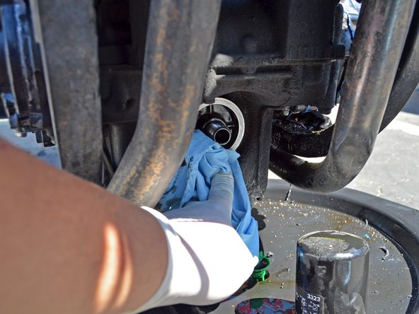 Wipe off all the oil from the engine's oil filter gasket face and threads using a clean rag or towel.