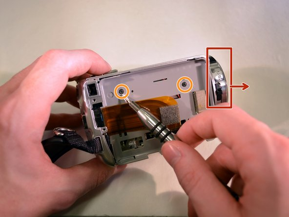 Hold the device securely in your left hand with the front lens facing right.