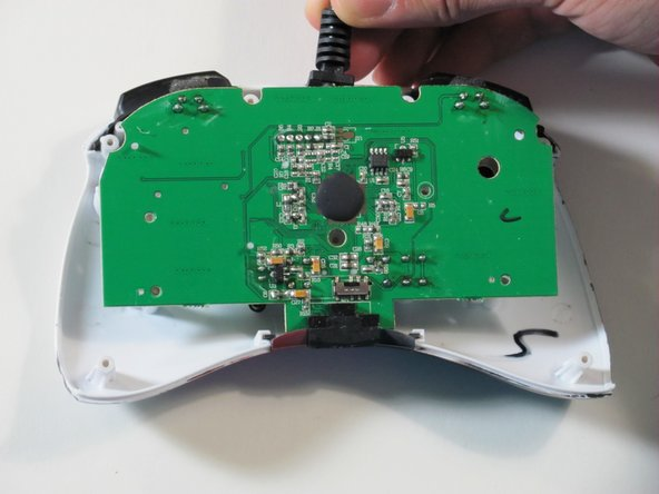 Hold the controller cable at the area just before it meets the controller and slowly lift upwards to slide it out of its plastic slot and remove the circuit board.