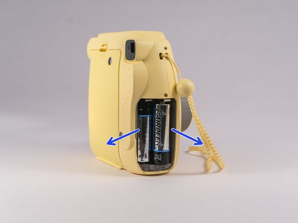 First, push in the lens and remove the two AA batteries.