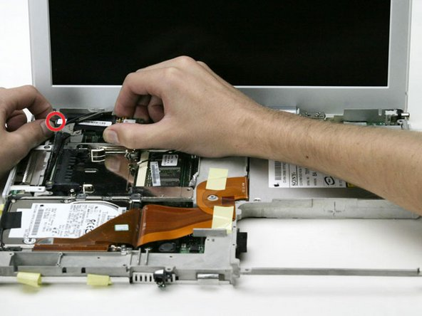 Lift the modem from the logic board on the right side, being careful not to strain the display data cable.