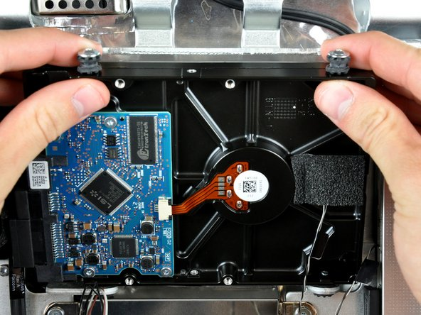 Rotate the top of the drive toward yourself, then lift the hard drive straight up off its lower pins.