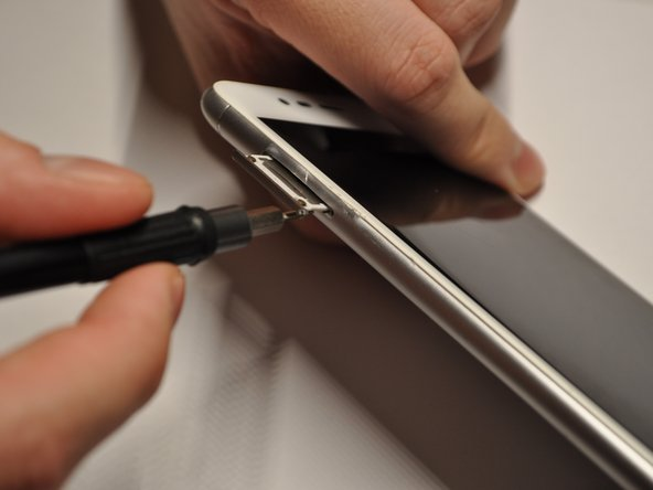Use the iFixit 150mm Flex Extension with the Hex 0.7 bit or the SIM card eject tool.