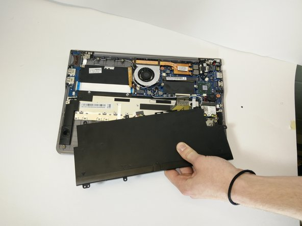 Image 2/2: Remove the battery from its position on the underside of the laptop.