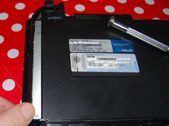 Image 1/2: Just below the DVD/CD drive, there are two little screws to remove.