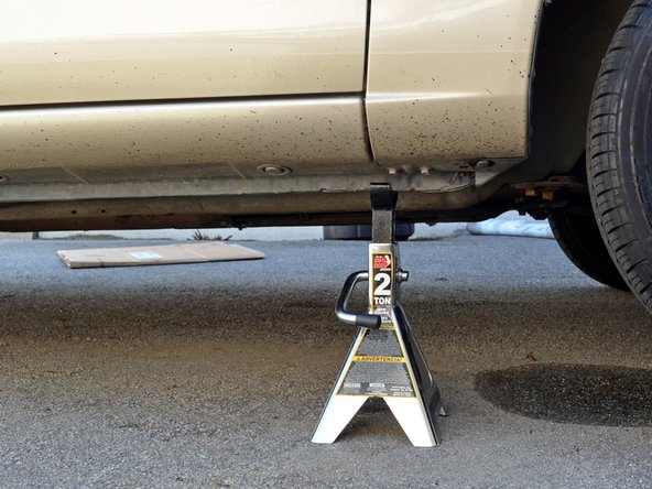 Image 3/3: Slowly lower the car until the jack stand supports the car and the jack does not. Remove the jack.