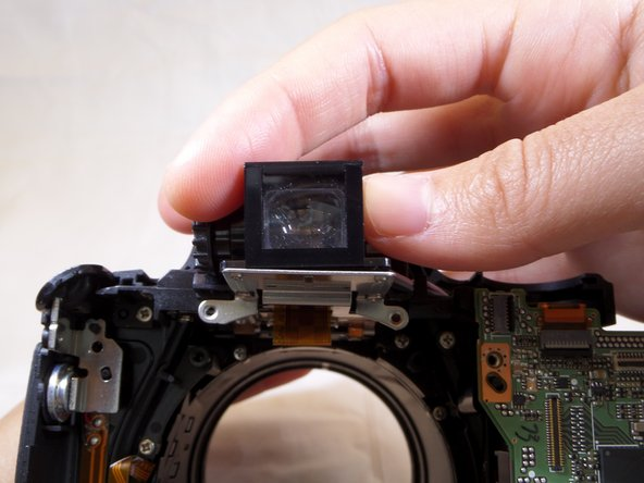 Vertically lift the viewfinder piece for removal.