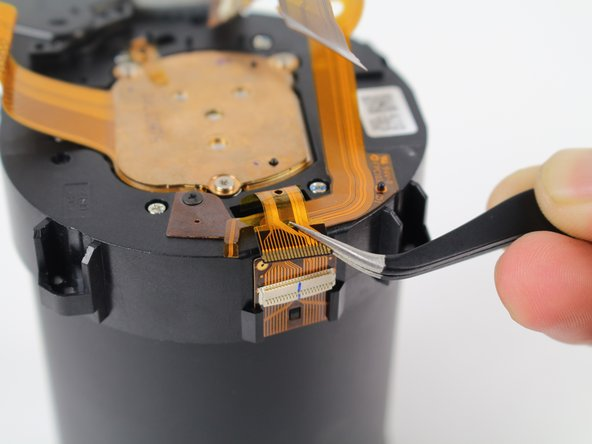 Using tweezers, very carefully pull to disconnect the ZIF connector ribbon on the side of the lens.