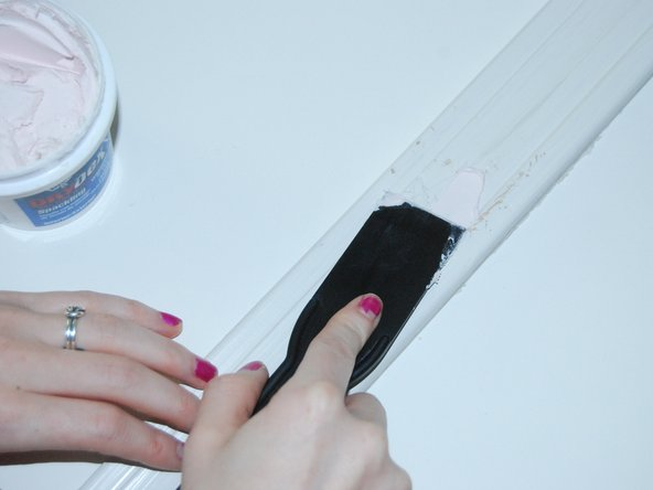 "Apply Dap drydex spackling to to the damaged area of the trim using a 1"" plastic putty knife."
