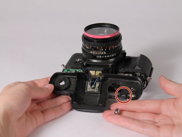 Place the shutter release button pieces into the indicated spot. The larger piece goes in first, then the smaller piece fits into that one.