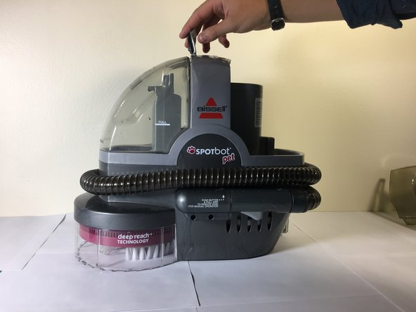 Lift the tap on top of the vacuum, and then remove the container on the left side of the vacuum.