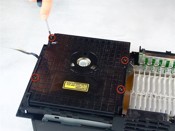 Image 1/2: Lift and remove the lid from the optical disc drive.