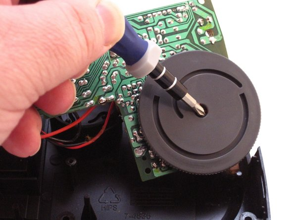 Image 2/2: Using a Phillip's #01 Screwdriver, unscrew the one 3mm screw from the middle of the AM-FM switch dial.
