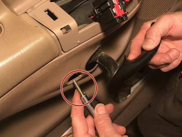 Using a 5/16 nut driver, unscrew the door handle by accessing the bolt inside the door panel.